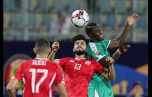 Senegal's Henri Grégoire Saivet (right) jumps for the ball with Tunisia's Ferjani Sassi (centre) during their teams' African Cup of Nations semi-final match yesterday.