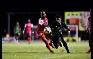Jamaica's Nicque Daley (right) on the attack as Salas Cannonier of St Kitts and Nevis looks on  at the Anthony Spaulding Sports Complex yesterday.
