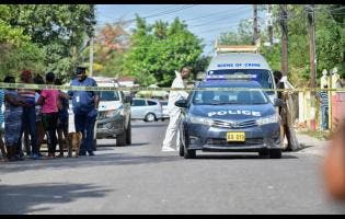 Police cordon off the scene of a murder-suicide on Waltham Park Road, St Andrew, on April 10.