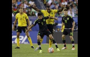 Mexico's Jesus Corona (9) tries to keep Jamaica's Wes Morgan (4) at bay during the first half of the Concacaf Gold Cup championship  match on July 26, 2015.