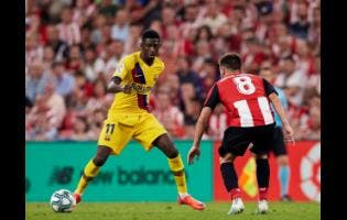 Barcelona's Ousmane Dembélé (left) duels for the ball with Athletic Bilbao's Unai Lopez during the Spanish La Liga  match between their teams at San Mames stadium last  Friday.