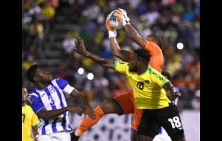 Honduran player Maynor Figueroa looks on while goalkeeper Luis Lopez takes the ball ahead of Jamaica's Brian Brown in their Concacaf Gold Cup match held at the National Stadium on June 18, 2019.