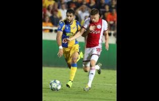 Ajax's Razvan Marin (right) challenges for the ball with APOEL's Musa Suleiman during the Champions League qualifying play-off first-leg  match between APOEL Nicosia and AFC Ajax yesterday.