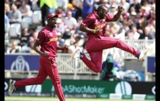 West Indies' Andre Russell (right) celebrates after dismissing Australia's Usman Khawaja during their ICC World Cup match at Trent Bridge in Nottingham, England, on Thursday, June 6, 2019.