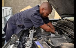 Harrison works on a car for a client.