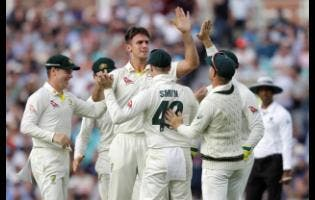 Australia's Mitchell Marsh celebrates taking the wicket of England's Sam Curran (centre) during the first day of the fifth Ashes Test match between England and Australia at the Oval cricket ground in London yesterday.