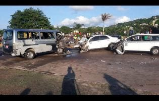 Onlookers view the crash scene in Montego Bay yesterday. Two of the drivers were killed.