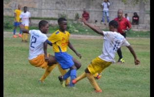 Kino Bryan  (centre) from Penwood High School tries to get away from the Northern Technical High School pair of Juvante Ricketts (right) and Jahiem Mckenzie during their aborted Manning Cup football match yesterday.