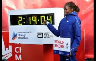 Brigid Kosgei of Kenya poses with her time after breaking the world record with a time of 2:14:04 during the Chicago Marathon yesterday.