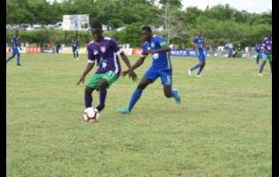 William Knibb Memorial High School's Deano Thomas (left) is tracked by Cedric Titus High School's Javel Green in their ISSA/WATA DaCosta Cup Group C encounter at William Knibb on September 17.