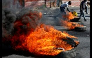 A man adds debris to a barricade of burning tyres set by protesters in the Delmar area of Port-au-Prince, Haiti, on Monday. Haiti's embattled president faced a fifth week of protests as roadblocks went up across the country after opposition leaders said they would not back down on their call for Jovenel Moïse to resign.
