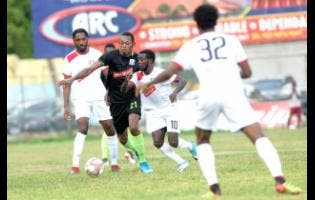 Kemar Seivwright of Molynes United FC (second left) under immense pressure from Arnett Gardens' Kimani Arbouine (left) and Paul Wilson  during a Red Stripe Premier League  encounter at the Drewsland Stadium on Sunday, September 22.