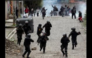 Supporters of former President Evo Morales clash with police in La Paz, Bolivia, yesterday. Morales resigned on Sunday under mounting pressure from the military and the public after his re-election victory triggered weeks of fraud allegations and deadly demonstrations.