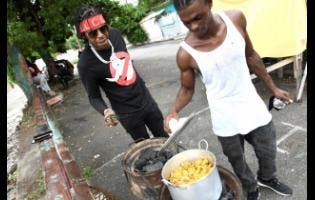 Savage's childhood friend, Kemar Smith, aka 'Famo', checks on the pot while the deejay looks on.