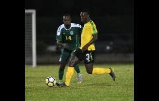 Jamaica's Kevaughn Isaacs dribbles away from Guyana's Daniel Wilson during their Nations League match at the Montego Bay Sports Complex last night.