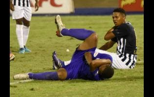 Kingston College's Khalifah Richards (left) goes down clutching his face after he was slapped by Jamaica College's Shadane Lopez, who retaliated after being bitten on the shoulder during their ISSA/Digicel Manning Cup semi-final at the National Stadium in St Andrew last night.