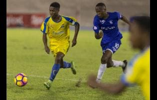 Clarendon College's Lamar Walker dribbles past Kingston College's Trayvone Reid in the Olivier Shield match last season.