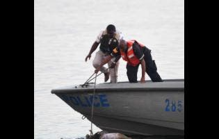 Marine police retrieve the unidentified body from the Kingston Harbour in the vicinity of Flag Circle, off Port Royal Street. According to the Kingston Central police, they were alerted about the body at 3:45 yesterday afternoon.