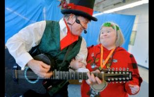 Jack Stanton (left) performing as Jack Frost, sings Christmas songs to Betty Diener during the annual Tri-State Civitan Club's holiday show at The Mac Center at Arc of Washington County in Hagerstown, Maryland, yesterday. The club has been entertaining children and adults with disabilities twice a year for about 25 years.
