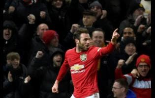 Manchester United's Juan Mata celebrates after scoring  during the English FA Cup third-round replay match between Manchester United and Wolverhampton Wanderers at Old Trafford in Manchester, England yesterday.