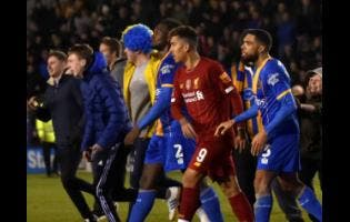 Liverpool's Roberto Firmino (second right) leaves the field at the end of the English FA Cup fourth-round match between Shrewsbury Town and Liverpool at the Montgomery Waters Meadow in Shrewsbury,  yesterday.