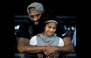 In this July 26, 2018 file photo former Los Angeles Laker Kobe Bryant and his daughter Gianna watch during the US national championships swimming meet in Irvine, California. Bryant, the 18-time NBA All-Star, who won five championships and became one of the greatest basketball players of his generation during a 20-year career with the Los Angeles Lakers, died in a helicopter crash yesterday.