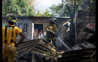 Firefighters perform cooling-down operation after in Vietnam, an area located off Grants Pen Drive in St Anrdew, where three houses were destroyed yesterday.