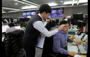 A currency trader checks the temperature of his colleague at the foreign exchange dealing room of the KEB Hana Bank headquarters in Seoul, South Korea, on Thursday. Asian shares were mixed Thursday after Wall Street recovered to record highs, but worries continued about the damage to the regional economy from the new virus that began in China.