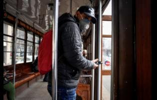 A man wears a sanitary mask as he steps off an empty tram in downtown Milan, Italy, yesterday.