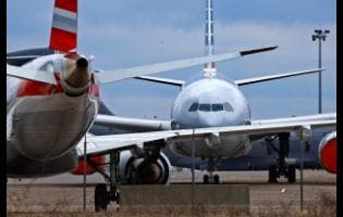 American Airlines planes are parked at Pittsburgh International Airport yesterday. The Jamaican Government is trying to track down more than 5,000 people who came into the island between March 18 and 23 as it seeks to contain the spread of the novel coronavirus.