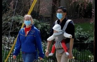 A couple out for walk wear protective masks on a warm afternoon in Pittsburgh yesterday. AP
