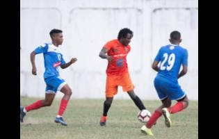 Rodico Wellington (centre) of Tivoli Gardens goes on the attack against opponents from Portmore United in the Red Stripe Premier League at Spanish Town Prison Oval earlier this season.