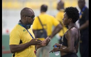 Coach Okeil Stewart  and Rushell Clayton talk during a training session before the World Athletics Championships last year.