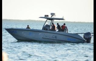 Marine police take a fisherman away in the vicinity of the Rae Town Fishing Village yesterday.
