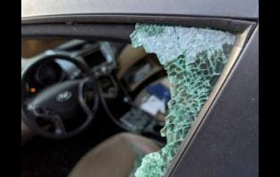 A parked car with a broken front window after a smash-and-grab break-in in Los Angeles.