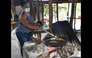 Michelle Fritz prepared fish for her customers in Scotts Cove, which sits on border of St Elizabeth and Westmoreland last Friday. She said that with the easing of the curfews, this is now their Easter as sales are gradually improving.