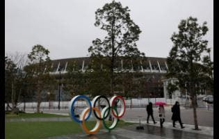 People walk by the Olympic rings near the new National Stadium in Tokyo, Japan, on Wednesday, March 4.