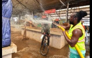 A Rastafarian who goes by the name Incient I, an employee of the  Kingston & St Andrew Municipal Corporation, washes a section of the Coronation Market in downtown Kingston yesterday. The market was cleaned as part of Labour Day activities in the capital city.