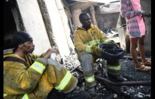 Firefighters A. Gosling (left) and F. Gordon take a breather at the scene of a fire on Rum Lane in Kingston yesterday.
