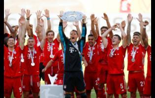 Bayern Munich's team captain Manuel Neuer lifts the trophy after  the German Bundesliga match between VfL Wolfsburg and FC Bayern Munich in Wolfsburg, Germany, Saturday, June 27, 2020.