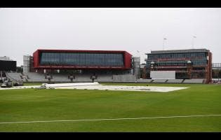 A general view of the covers and out-field as the start of play is delayed due to rain, during day one of a West Indies Warm Up match at Old Trafford in Manchester, England, yesterday ahead of their upcoming three-match Test series against the hosts.