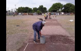 Team manager Ronny Lyons (foreground) works on a cricket pitch in the community of Majesty Gardens, otherwise called 'Back-To'. Lyons is responsible for the creation of a new cricket team in the volatile community, which he hopes will help to stem violence in the area.
