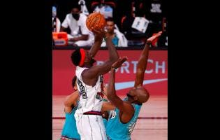 Toronto Raptors' Pascal Siakam, front left, shoots over Memphis Grizzlies' Anthony Tolliver, right, during the second quarter of an NBA basketball game Sunday, Aug. 9, 2020, in Lake Buena Vista, Florida.