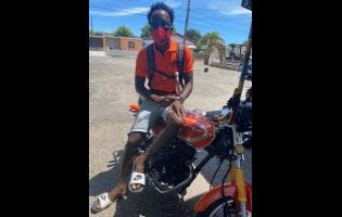 PNP supporter Junior Gayle shows off his orange motorbike.