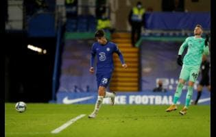 Chelsea's Kai Havertz (left) dribbles past Barnsley goalkeeper Brad Collins to score his team's third goal during their English League Cup third-round match at Stamford Bridge in London, England,  yesterday.