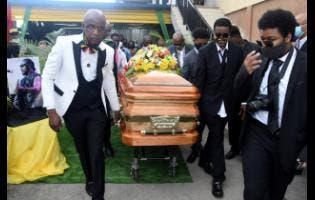 Peter Perry (left) CEO of Perry's Funeral Home leads the  pall bearers in carrying the casket containing the body of the late Frederick 'Toots' Hibbert.