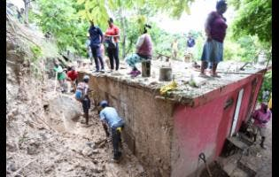 Shooters Hill residents try to find Sanique Leachman after she was buried under mud and debris after a landslide.