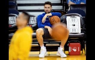 AP In this June 4, 2019 file photo, Golden State Warriors' Klay Thompson sits on the bench watching teammates during practice for the NBA Finals against the Toronto Raptors in Oakland, California.