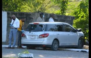 Police search the vehicle in which three gunmen were using in Portmore yesterday, allegedly to carry out a murder in Waterford.