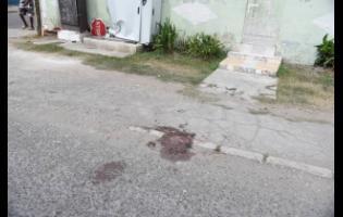 Blood stains the sidewalk where three men were shot in Arnett Gardens on Monday afternoon.